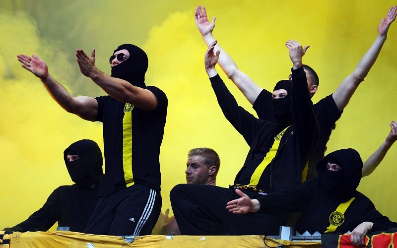 GELSENKIRCHEN, GERMANY - OCTOBER 26: Fans of Dortmund trow flares and firework prior to the Bundesliga match between FC Schalke 04 and Borussia Dortmund at Veltins-Arena on October 26, 2013 in Gelsenkirchen, Germany.  (Photo by Lars Baron/Bongarts/Getty Images)